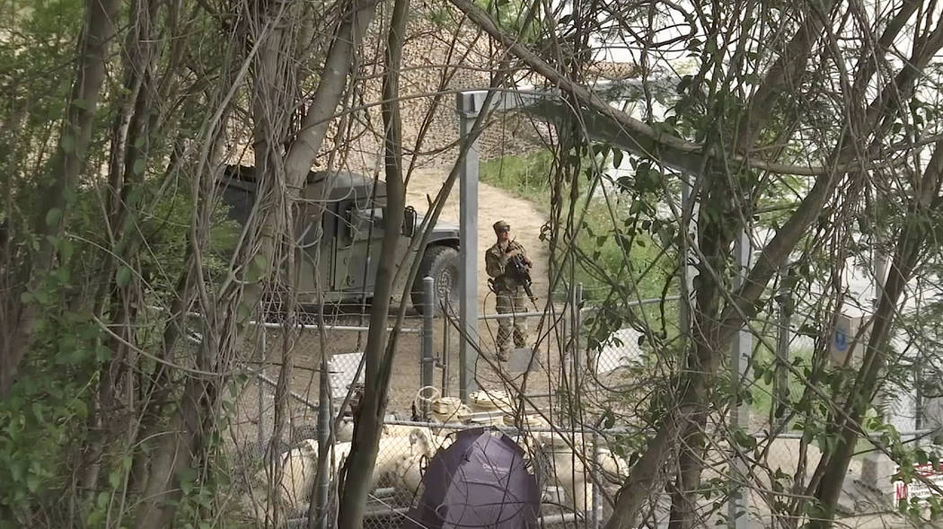 In this April 10, 2018 frame from video, a National Guard troop watches over Rio Grande River on the border in Roma, Texas. The deployment of National Guard members to the U.S.-Mexico border at Pr ...