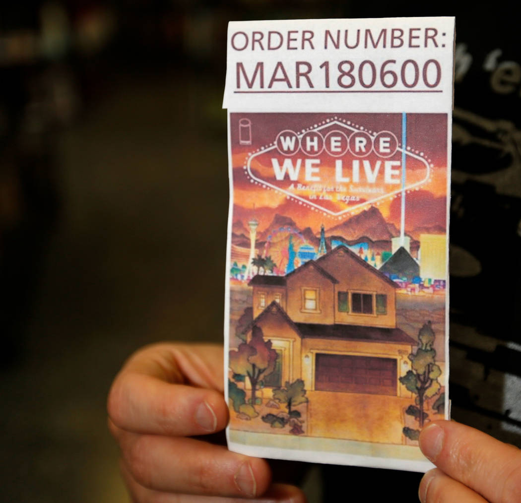 """J.H. Williams III, a comic artist, holds a cover copy of their project, """"Where We Live,"""" a comic anthology, at Alternate Reality Comics in Las Vegas, Wednesday, April 11, 2018. The comi ..."""