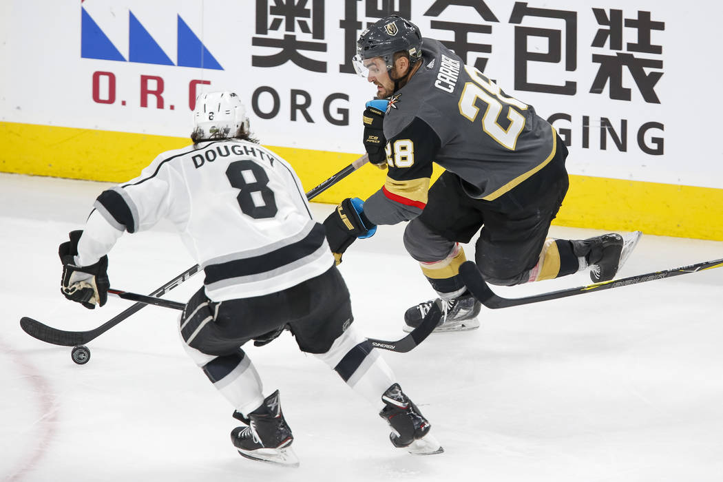 Golden Knights left wing William Carrier (28) skates with the puck as Los Angeles Kings defenseman Drew Doughty (8) closes in during the third period of Game 1 of an NHL hockey first-round playoff ...
