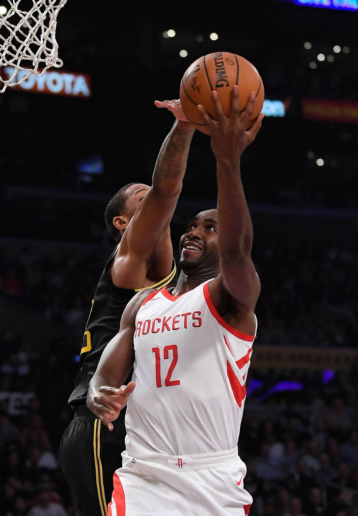 Houston Rockets forward Luc Mbah a Moute, right, shoots as Los Angeles Lakers forward Channing Frye defends during the first half of an NBA basketball game Tuesday, April 10, 2018, in Los Angeles. ...