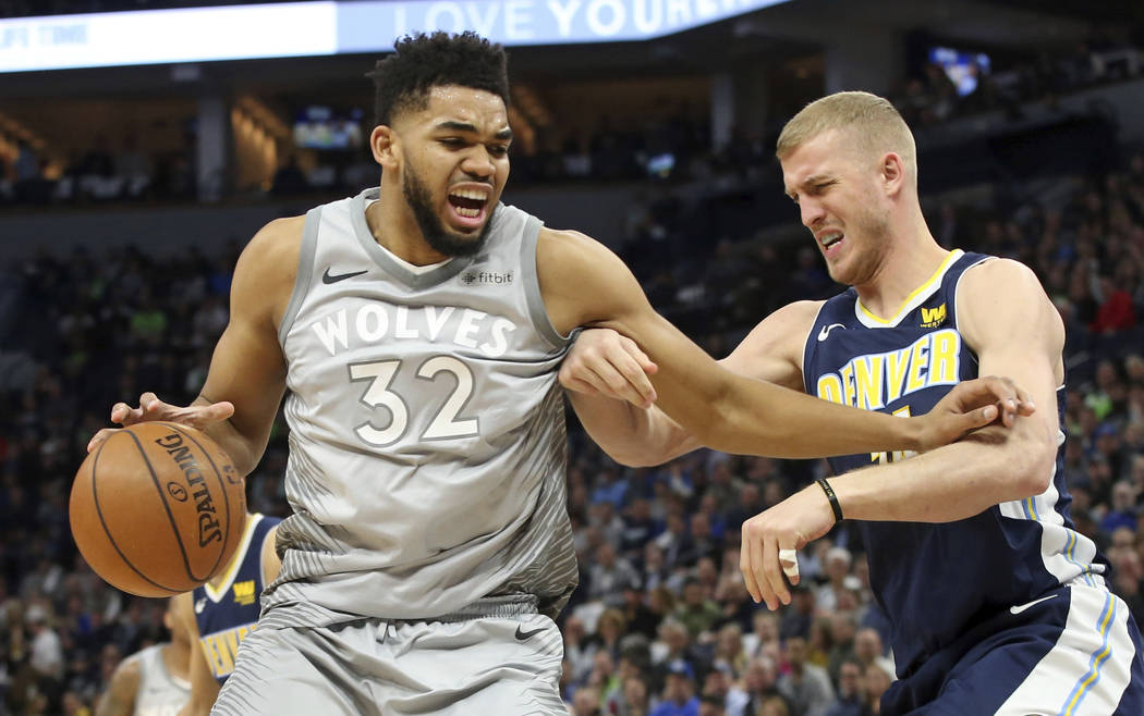 Minnesota Timberwolves' Karl-Anthony Towns, left, tries to keep Denver Nuggets' Mason Plumlee at bay during the first half of an NBA basketball game Wednesday, April 11, 2018, in Minneapolis. (AP  ...