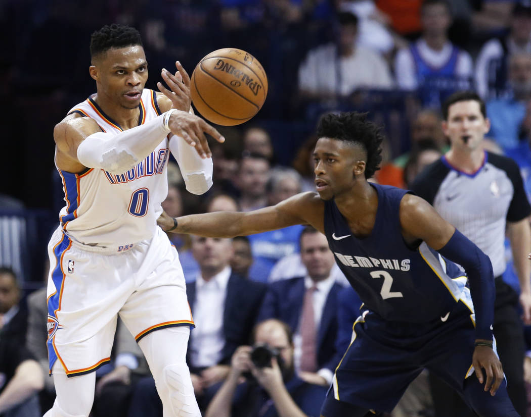 Oklahoma City Thunder guard Russell Westbrook (0) passes the ball in front of Memphis Grizzlies guard Kobi Simmons (2) during the first half of an NBA basketball game in Oklahoma City, Wednesday,  ...