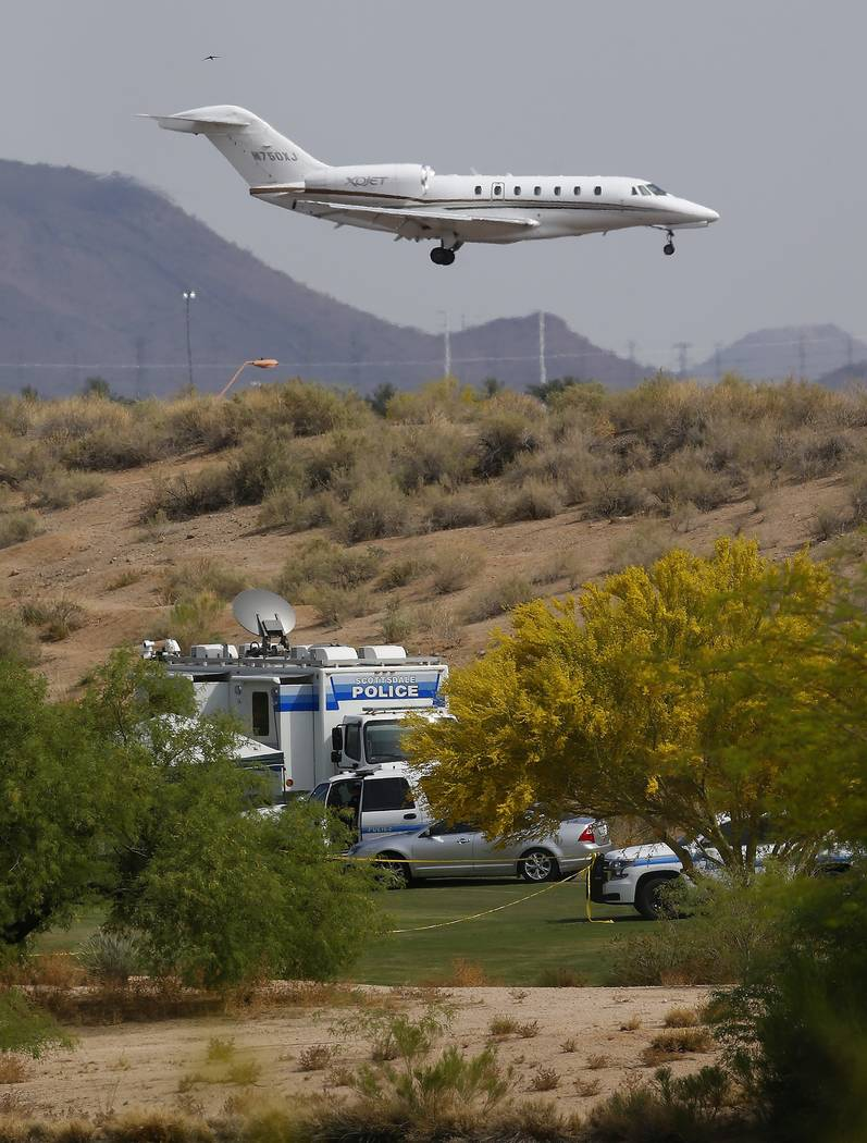 As a jet comes in for a landing at Scottsdale Airport, authorities park on a golf course near the site of a plane crash that killed several people Tuesday, April 10, 2018, in Scottsdale, Ariz. (AP ...