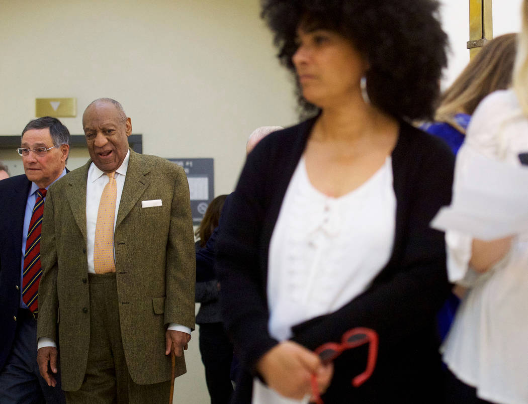 Bill Cosby walks towards the courtroom after a break near Lili Bernard, right, in the Montgomery County Courthouse during Cosby's sexual assault retrial on Thursday, April 12, 2018, in Norristown, ...