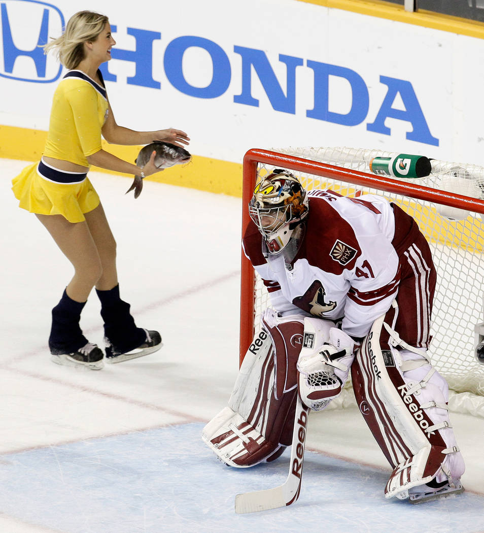 In this May 2, 2012, file photo, a Nashville Predators ice girl skates past Phoenix Coyotes goalie Mike Smith (41) as she carries a catfish off the ice after it was thrown from the stands during G ...