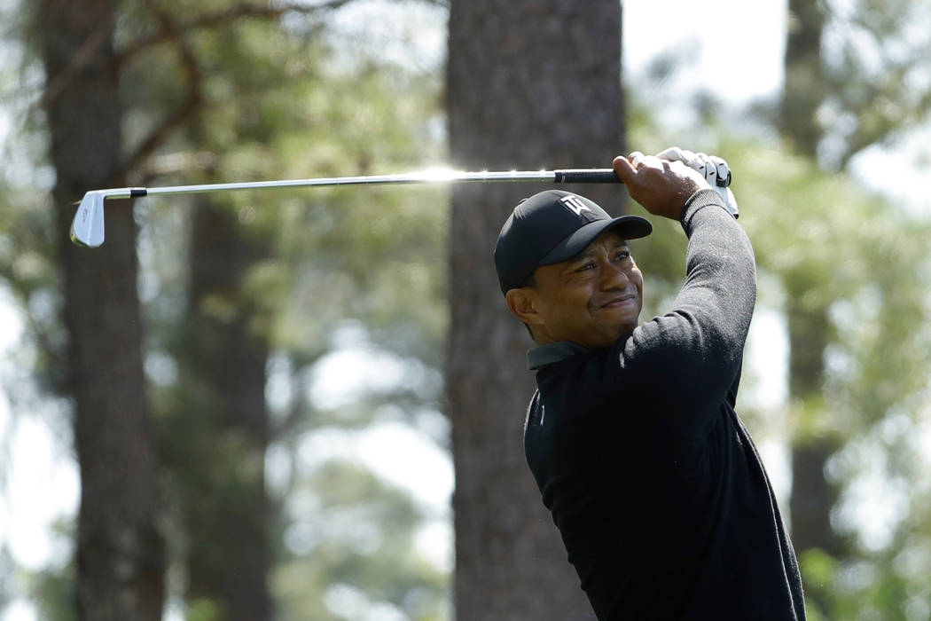 In this April 5, 2018, file photo, Tiger Woods hits a shot on the fourth hole during the first round at the Masters golf tournament in Augusta, Ga. (AP Photo/Matt Slocum, File)