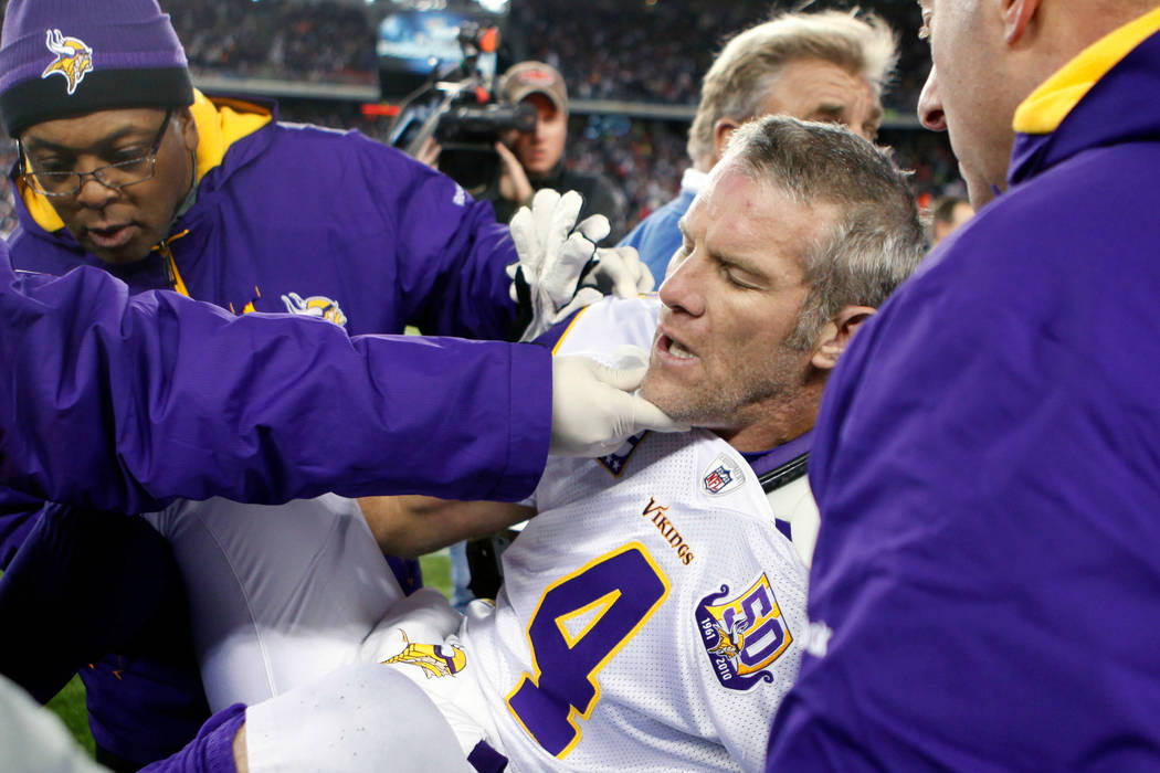In this Oct. 31, 2010, file photo, Minnesota Vikings quarterback Brett Favre, center, is helped onto a cart to be taken off the field after a hit from New England Patriots' Myron Pryor during the ...