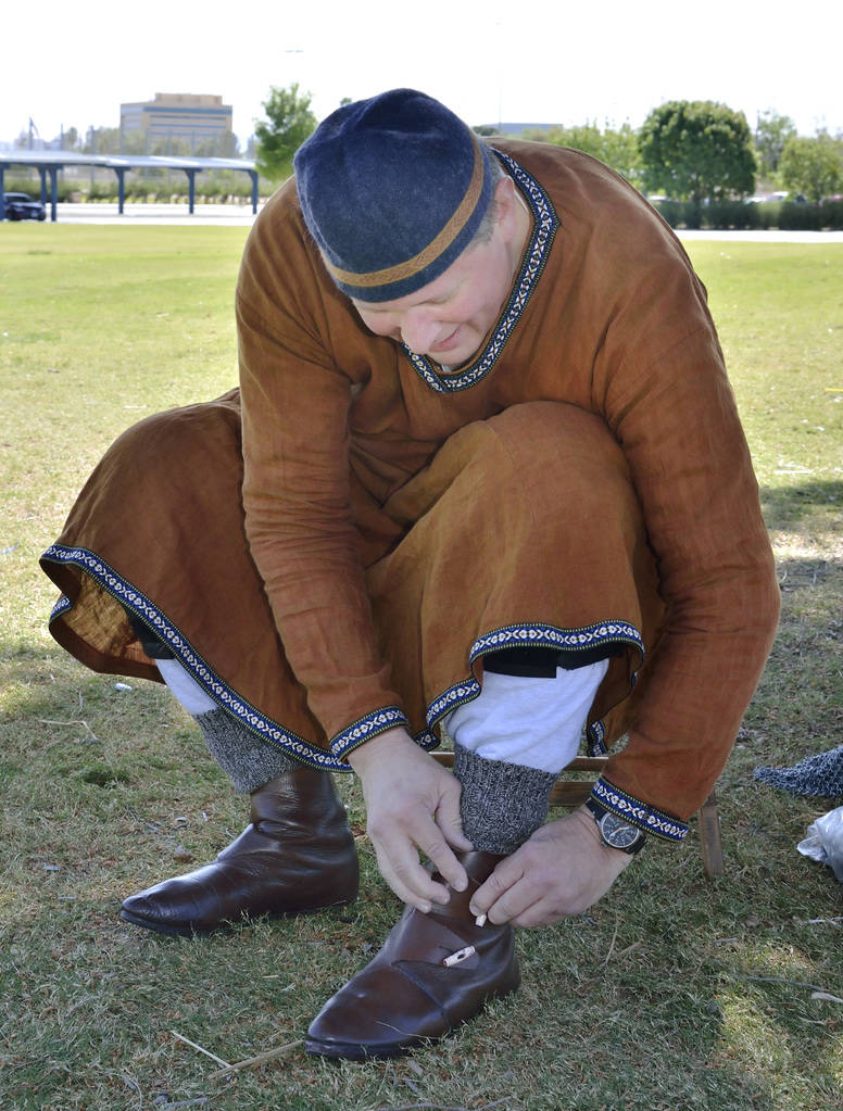 """Rick Mikkelsen puts on his boots before participating in a demonstration of """"How to Fight Like a Viking"""" sponsored by the Sons of Norway Vegas Vikings Lodge 6-152 at Lorenzi Park at ..."""