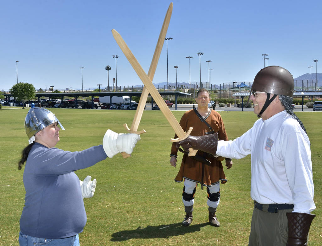 """Rick Mikkelsen, center, watches as Nivia Balsera, left, and Douglas Kittelson practice sword fighting during a demonstration of """"How to Fight Like a Viking"""" sponsored by the Sons of ..."""