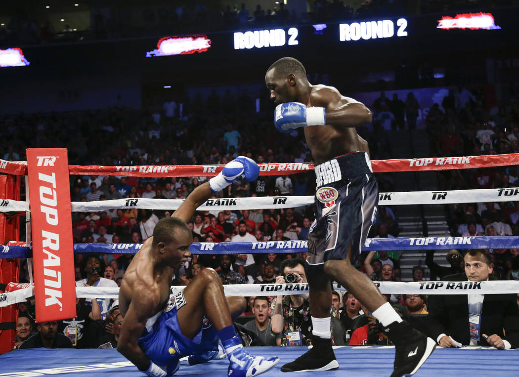 Terence Crawford stands over Julius Indongo, after a punch brought him down in the second round of a junior welterweight world title unification bout in Lincoln, Neb., Saturday, Aug. 19, 2017. Cra ...