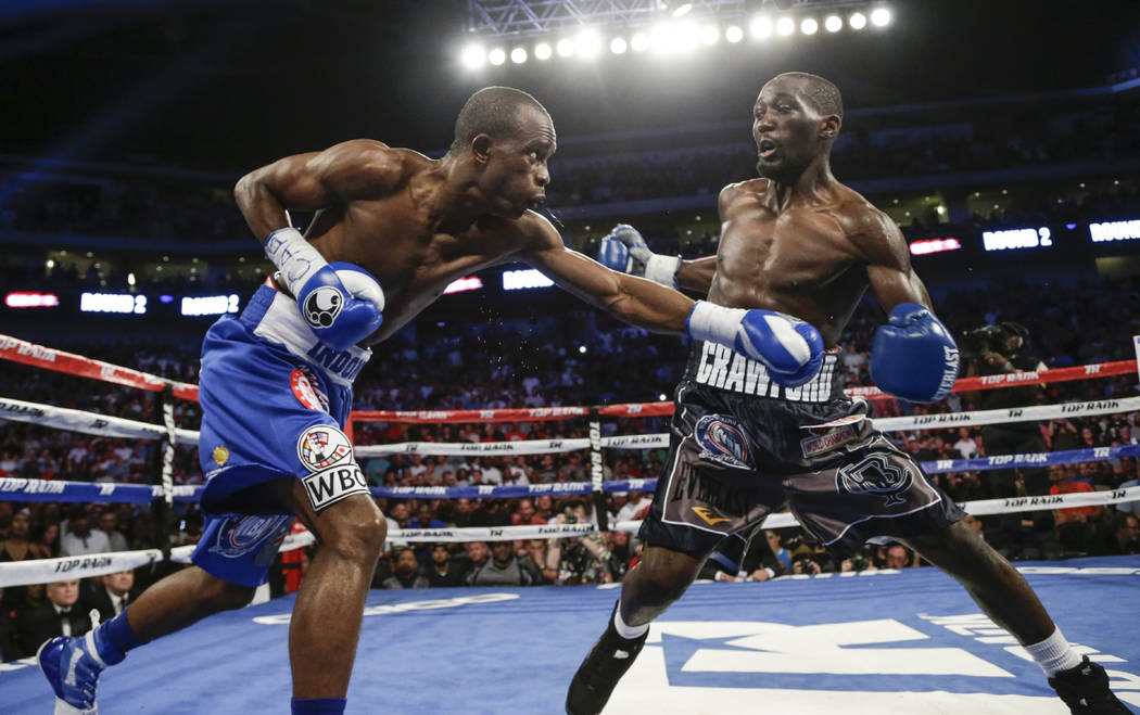 Terence Crawford, right, leans back from a punch from Julius Indongo during the second round of a junior welterweight title unification boxing bout in Lincoln, Neb., Saturday, Aug. 19, 2017. Crawf ...