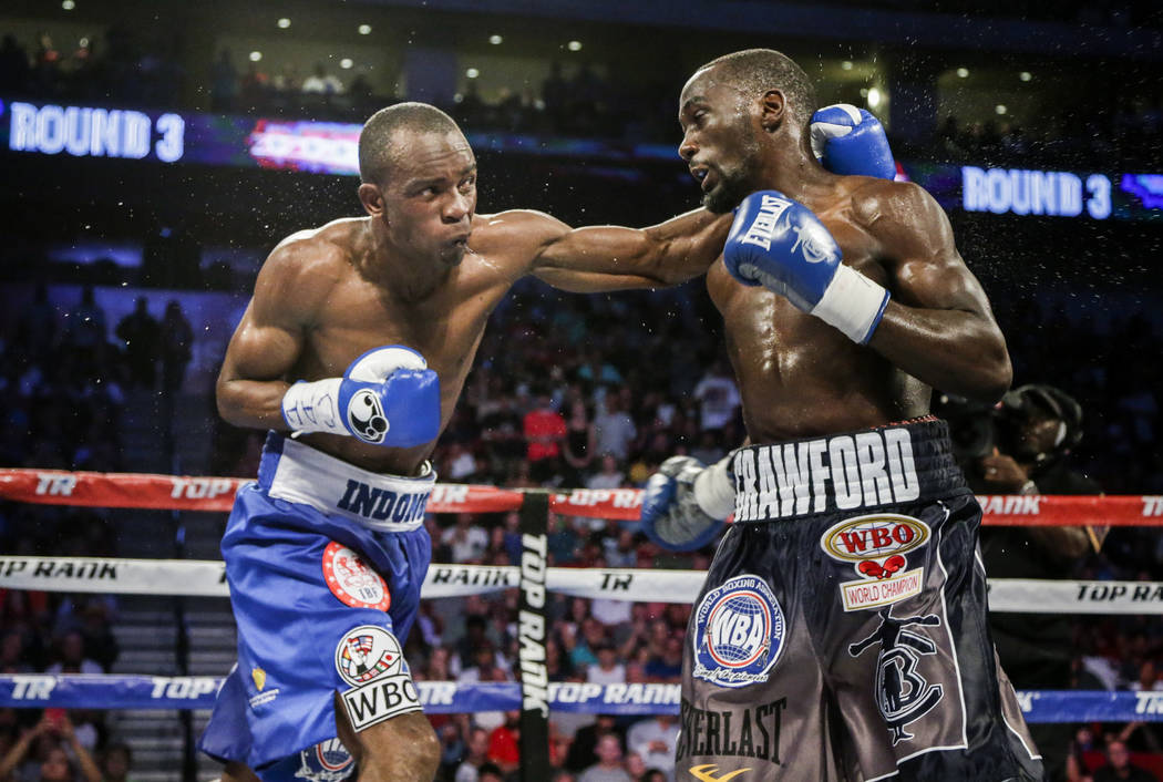 "Julius Indongo, left, connects with a punch against Terence ""Bud"" Crawford, in a junior welterweight world title unification bout in Lincoln, Neb., Saturday, Aug. 19, 2017. Crawford won ..."