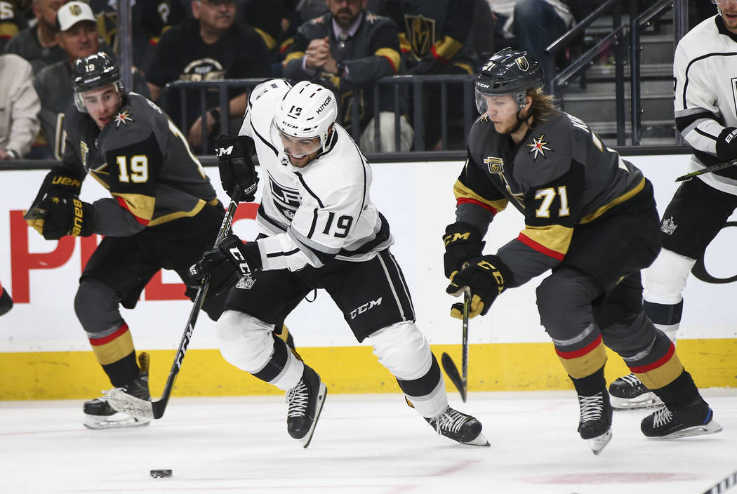 Los Angeles Kings center Alex Iafallo (19) moves the puck between Golden Knights center William Karlsson (71) and right wing Reilly Smith (19) during the second period of Game 1 of an NHL hockey f ...