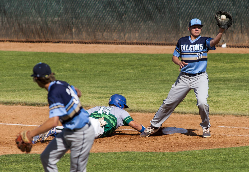 Green Valley's Jake Empey slides in safe at first while Foothill first baseman Tyler Kara catches the ball during the second inning at Green Valley High School on Thursday, April 12, 2018. Green V ...
