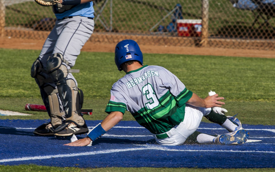 Green Valley's Callan Hermansen slides in safe at home while playing against Foothill in the fifth inning at Green Valley High School on Thursday, April 12, 2018. Green Valley won 5-3. Patrick Co ...