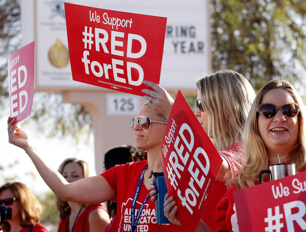 Teachers at Humphrey Elementary school participate in a state-wide walk-in prior to classes Wednesday, April 11, 2018, in Chandler, Ariz. Arizona teachers are demanding a 20 percent pay raise and ...