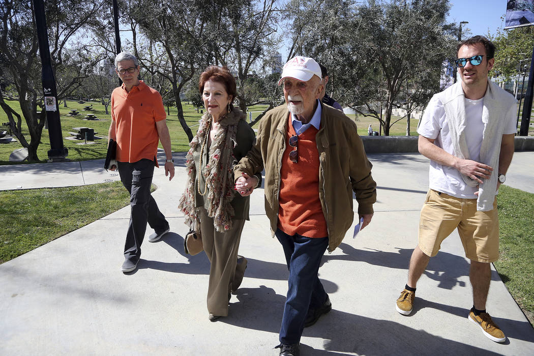 In this Wednesday, April 11, 2018, photo, childhood Holocaust survivors Simon Gronowski, center right, and Alice Gerstel Weit hold hands as they tour the Los Angeles Holocaust Museum. (AP Photo/Re ...