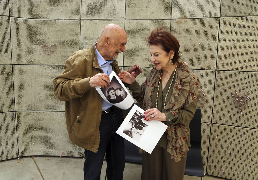 In this Wednesday, April 11, 2018, photo, childhood Holocaust survivors Simon Gronowski and Alice Gerstel Weit exchange photographs they haven't seen in decades, at the Los Angeles Holocaust Museu ...