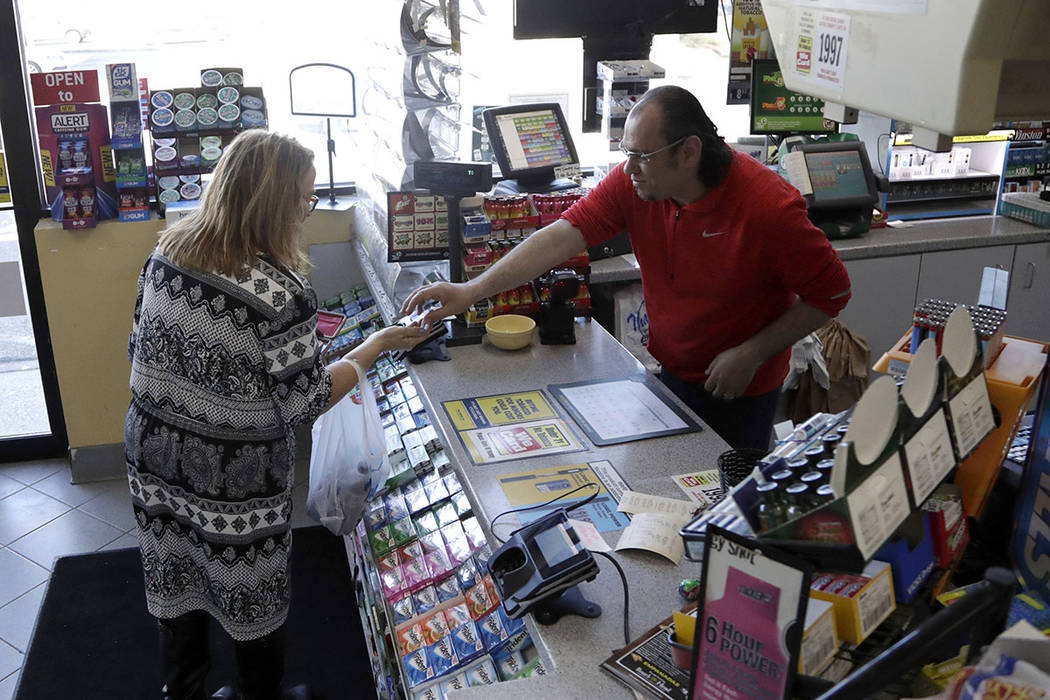 A cashier checks out a customer at a Lukoil service station where the winning ticket for the Mega Millions lottery drawing was sold, Saturday, March 31, 2018, in Riverdale, N.J. (AP Photo/Julio Co ...