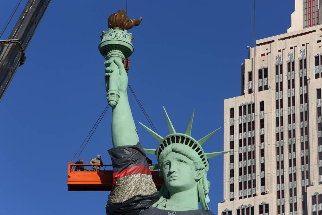 Workers install a Vegas Golden Knights jersey on the Statue of Liberty at New York-New York on Friday, April 13, 2018, on the Las Vegas Strip. (Bizuayehu Tesfaye/Las Vegas Review-Journal) @bizutesfaye
