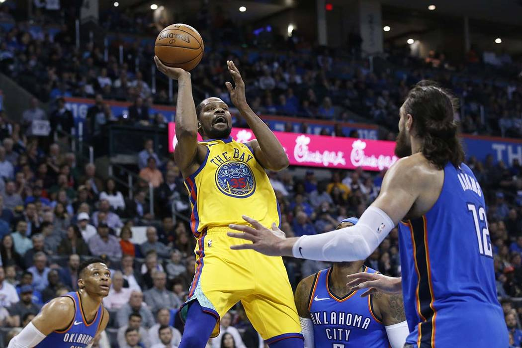 Golden State Warriors forward Kevin Durant (35) shoots between Oklahoma City Thunder guard Russell Westbrook, left, forward Carmelo Anthony, center, and center Steven Adams during the first half o ...