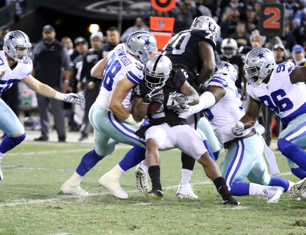 Oakland Raiders running back Marshawn Lynch (24) is tackled by Dallas Cowboys wide receiver Dez Bryant (88) during the first half of a NFL game in Oakland, Calif., Sunday, Dec. 17, 2017. Heidi Fan ...
