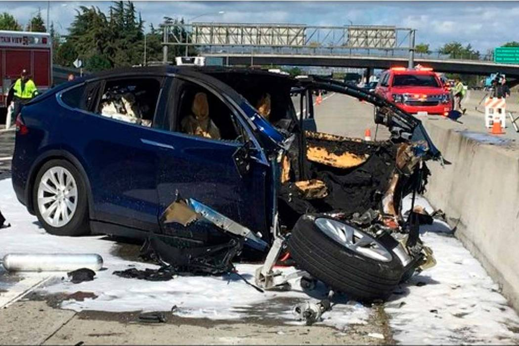 Emergency personnel work at the scene where a Tesla electric SUV crashed into a barrier on U.S. Highway 101 in Mountain View, Calif., on March 23. Federal safety investigators have booted electric ...