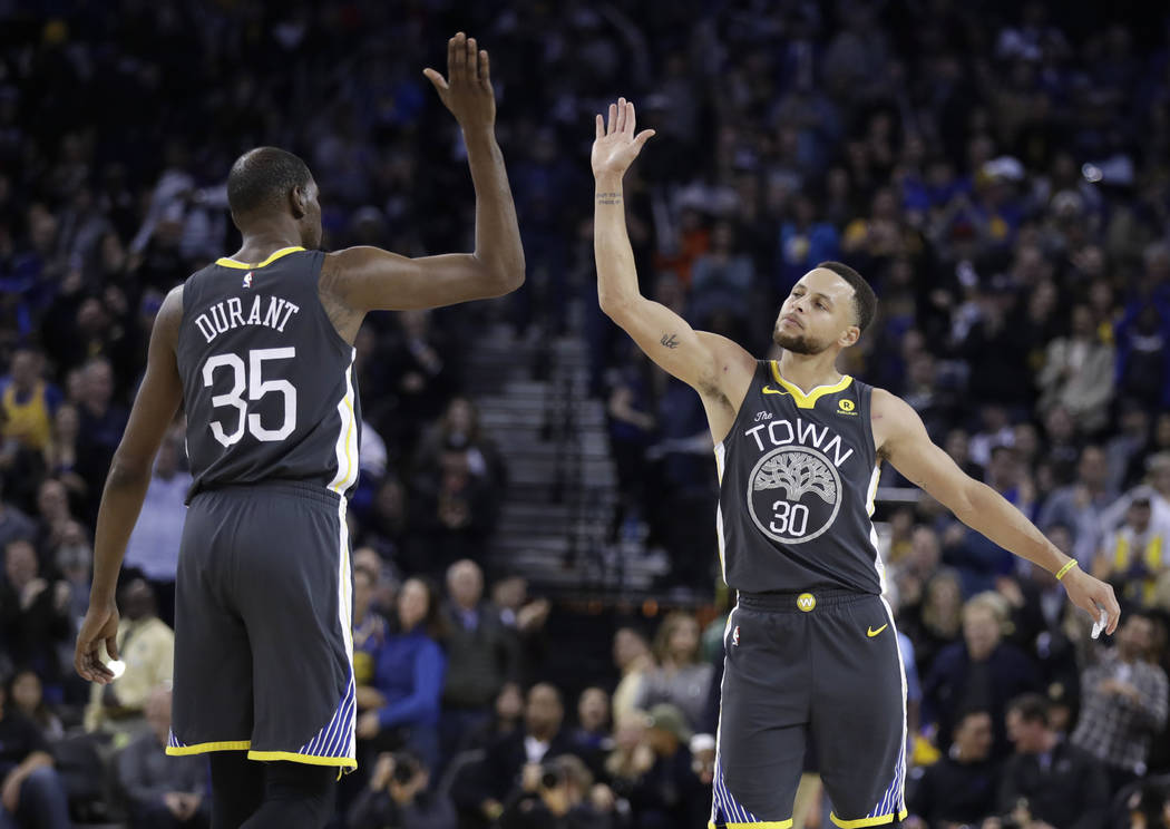 Golden State Warriors' Kevin Durant, left, celebrates after a basket by teammate Stephen Curry, right, during the second half of an NBA basketball game against the Los Angeles Clippers on Thursday ...