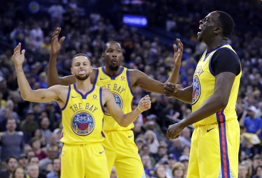 Golden State Warriors' Draymond Green, right, reacts as a foul is called against him next to teammates Stephen Curry, left, and Kevin Durant during the first half of an NBA basketball game against ...
