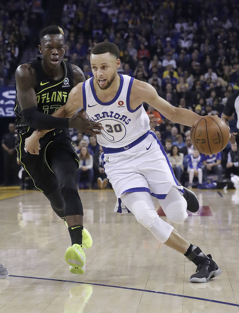 Golden State Warriors guard Stephen Curry (30) dribbles against Atlanta Hawks guard Dennis Schroeder during the first half of an NBA basketball game in Oakland, Calif., Friday, March 23, 2018. (AP ...