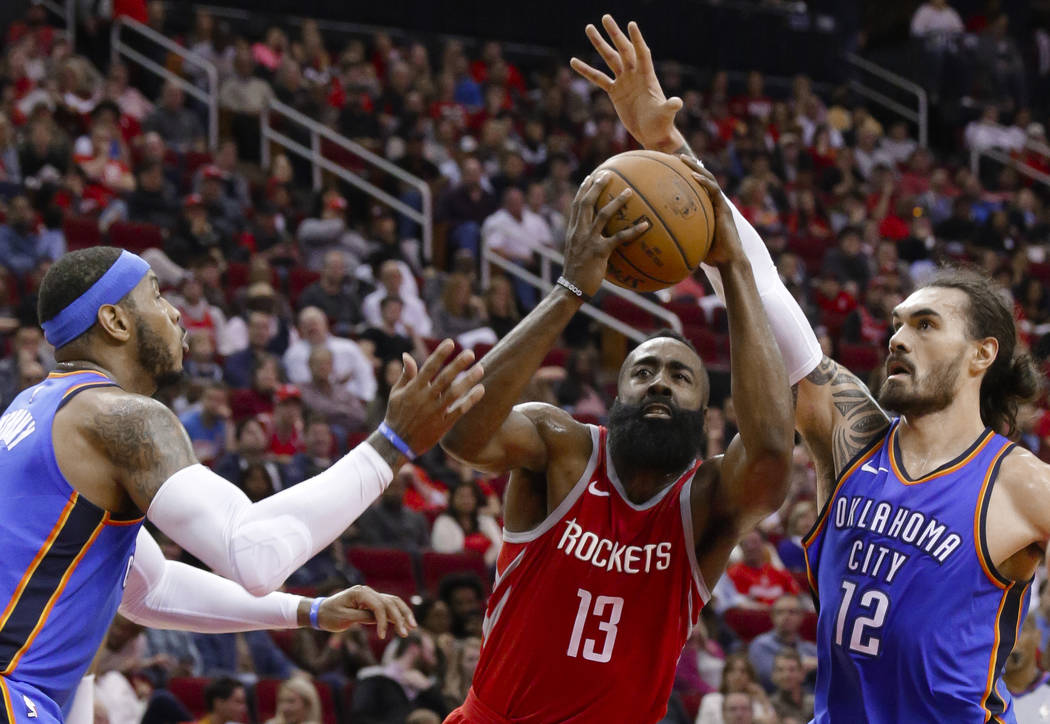 Houston Rockets guard James Harden (13) drives for a shot between Oklahoma City Thunder forward Carmelo Anthony, left, and center Steven Adams (12) during the second half of an NBA basketball game ...