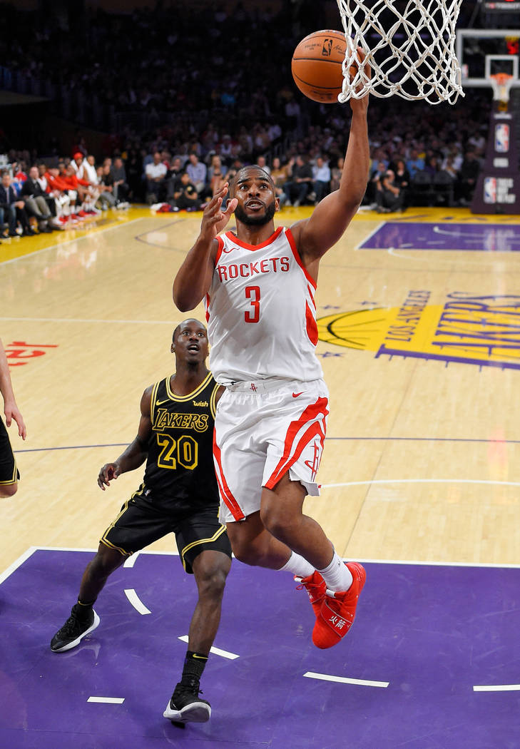 Houston Rockets guard Chris Paul, right, shoots as Los Angeles Lakers guard Andre Ingram defends during the second half of an NBA basketball game, Tuesday, April 10, 2018, in Los Angeles. The Rock ...