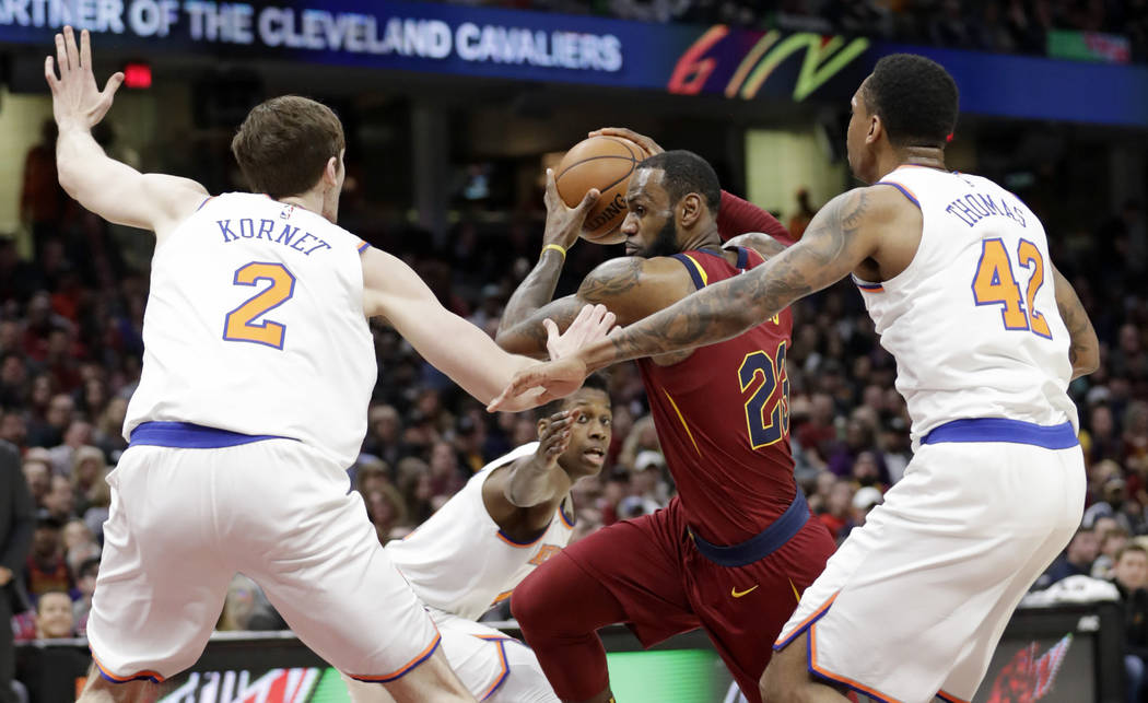 Cleveland Cavaliers' LeBron James, center, drives past New York Knicks' Luke Kornet, left, from Switzerland, and Lance Thomas in the first half of an NBA basketball game, Wednesday, April 11, 2018 ...