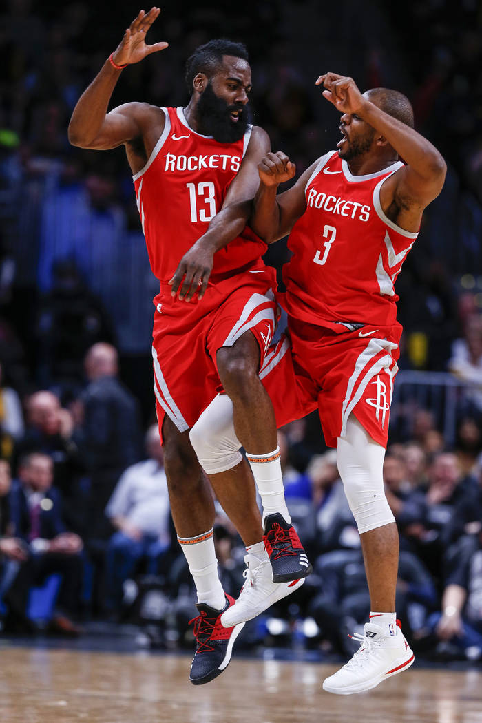 Houston Rockets guard James Harden (13) and Chris Paul (3) celebrate a three point shot during the fourth quarter of an NBA basketball game against the Denver Nuggets, Sunday, Feb. 25, 2018, in De ...