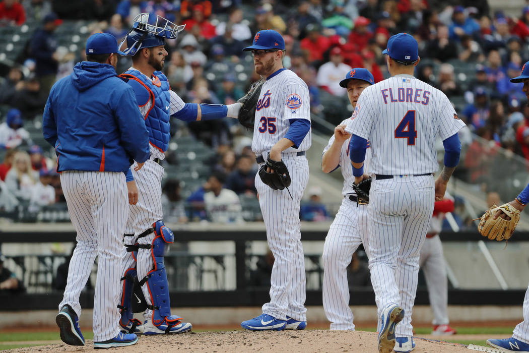 New York Mets manager Mickey Callaway, left, appraoches to the mound to fetch Mets relief pitcher Jacob Rhame (35) as Mets catcher Kevin Plawecki after consoles him during a baseball game, Sunday, ...