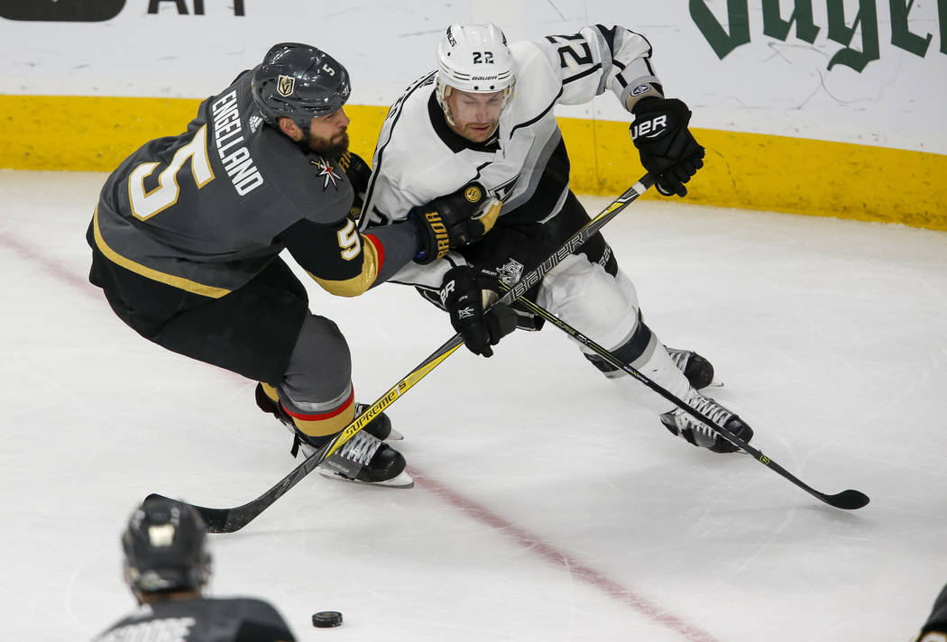 Los Angeles Kings center Trevor Lewis (22) skates with the puck as Golden Knights defenseman Deryk Engelland (5) defends during the third period of Game 2 of an NHL hockey first-round playoff seri ...
