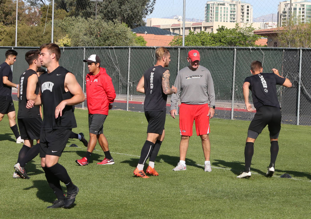 Rich Ryerson, UNLV soccer head coach, second right, and assistant coach Camilio Valencia, left, watch as their players warm up during team practice on Wednesday, April 18, 2018, in Las Vegas. Bizu ...