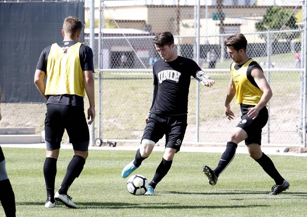 UNLV soccer midfielder Austin Manthey, center, kicks the ball between Adam Musovski, right, and Timo Mehlich during practice on Wednesday, April 18, 2018, in Las Vegas. Bizuayehu Tesfaye/Las Vegas ...