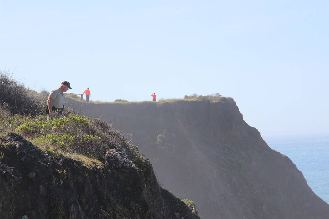 Deputy Bill Holcomb looks down the cliff near the crash site near Mendocino, Calif., as search and rescue volunteers scour the area behind him on Thursday, March 29, 2018, and resume looking for t ...