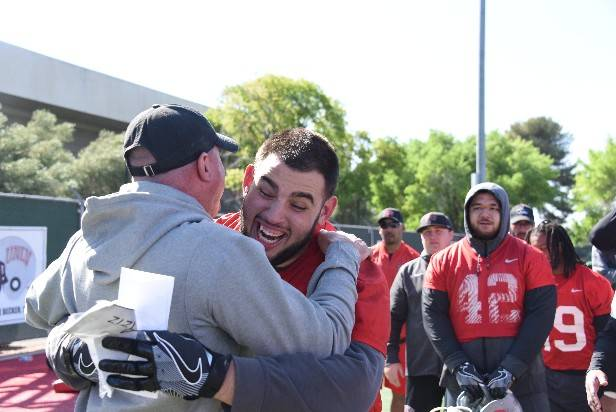 UNLV football coach Tony Sanchez congratulates senior defensive tackle Ammir Aziz on the scholarship. Photo courtesy of UNLV Athletics.