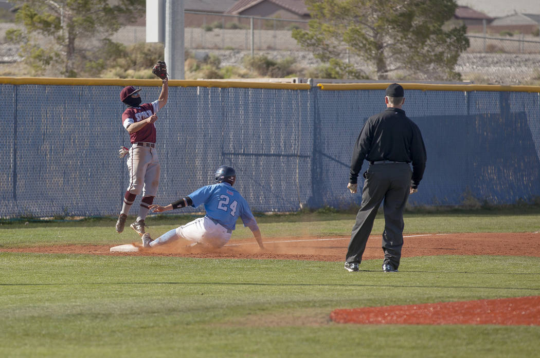 Cimarron-Memorial High School's Daniel Valdivia (1) jumps to catch the ball as Centennial High School's Michael Jones (24)slides to safety in a game at Centennial High School in Las Vegas, Friday, ...