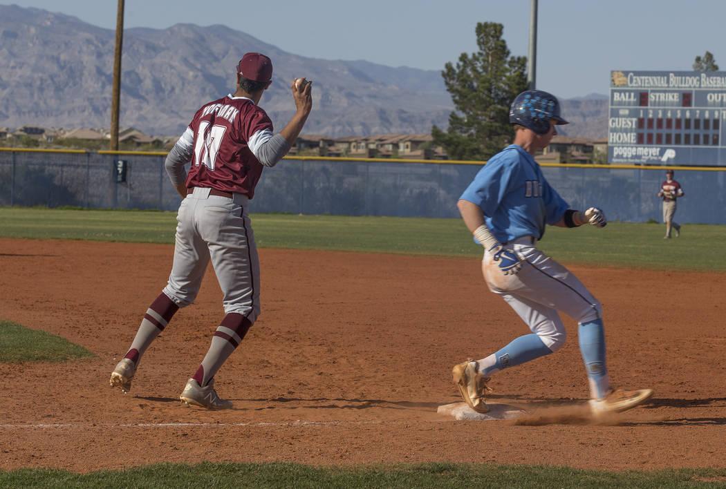 Cimarron-Memorial High School's Seth Hoffman (10) throws the ball as Centennial High School's Kian Wilbur (4) runs through first base in a game at Centennial High School in Las Vegas, Friday, Apri ...