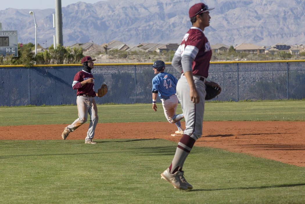 Centennial High School's Austin Kryszczuk (47) runs through second base as Cimarron-Memorial High School players wait to catch the ball in a game at Centennial High School in Las Vegas, Friday, Ap ...