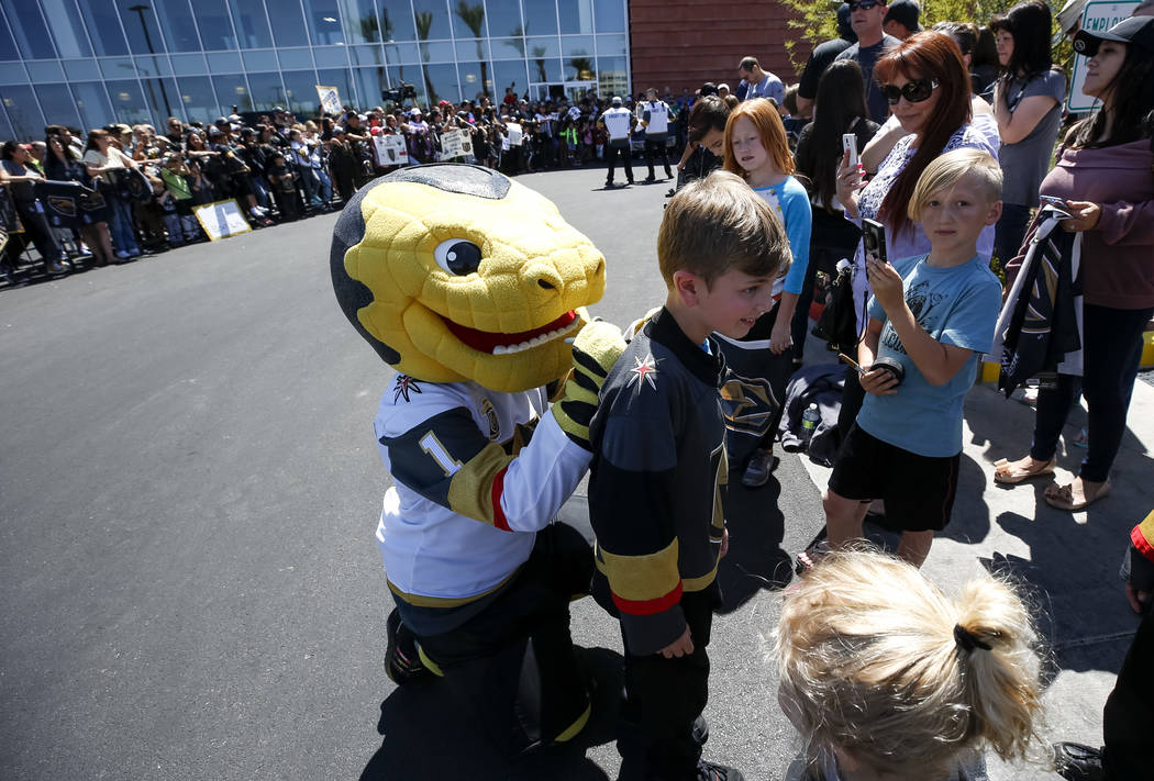 Vegas Golden Knights mascot Chance the Golden Gila Monster autographs a jersey for a young fan outside City National Arena during a send-off event ahead of games three and four of the NHL playoff ...