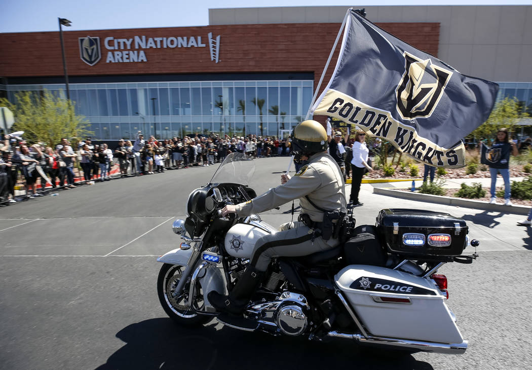 A police officer waives the Golden Knights flag outside City National Arena during a send-off event ahead of games three and four of the NHL playoff series against Los Angeles Kings on Saturday, A ...