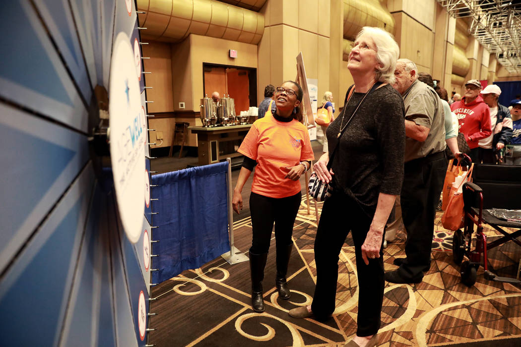 Rexanne Andrews, left, helps Rosie Weinrauch spin the wheel during the AgeWell Expo at the Rio Convention Center in Las Vegas on Saturday, April 14, 2018. Andrea Cornejo Las Vegas Review-Journal @ ...