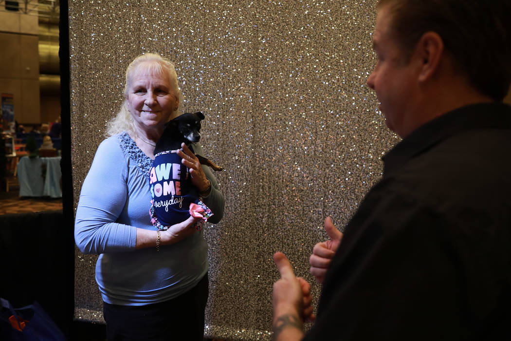 Robert Entrikin, of Vegas Booths, takes a photo of Jenie Williams and her 6-year-old chihuahua mix, Ginger, during the AgeWell Expo at the Rio Convention Center in Las Vegas on Saturday, April 14, ...