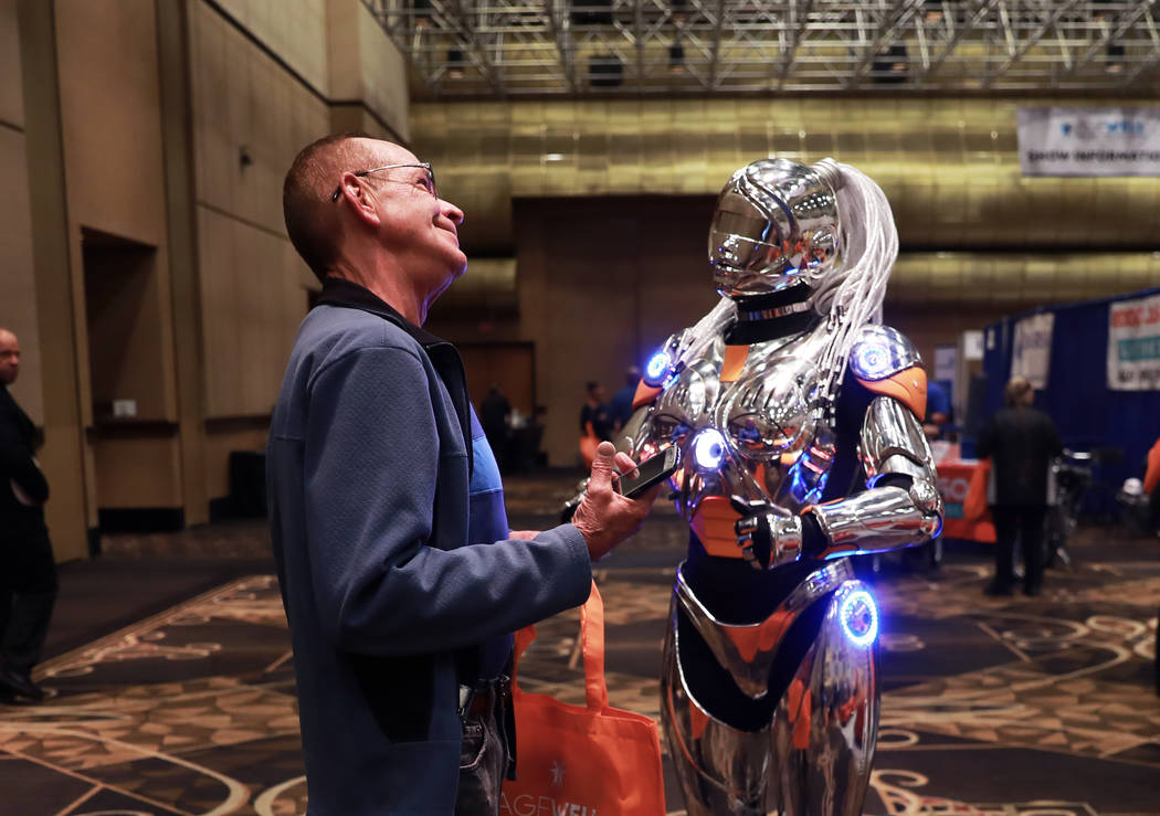 Gene Hickman, of Las Vegas, is greeted by a robot in front of the OptumCare exhibit during the AgeWell Expo at the Rio Convention Center in Las Vegas on Saturday, April 14, 2018. Andrea Cornejo La ...