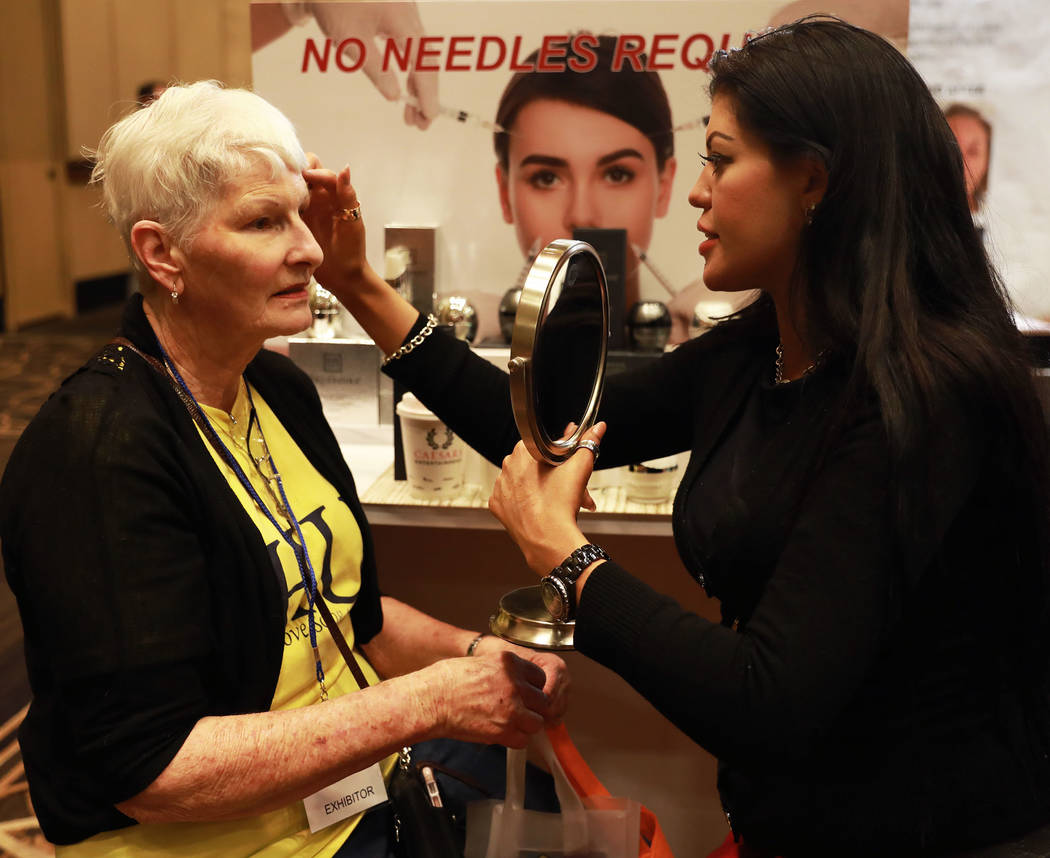 Karissa Munoz, a sales representative with Truffoire, right, applies a skin care product on JoAnna Rihyer during the AgeWell Expo at the Rio Convention Center in Las Vegas on Saturday, April 14, 2 ...