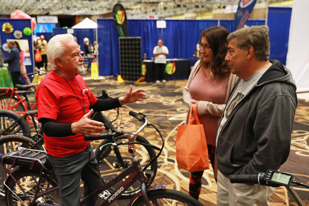 Howard Hicks, of Pedego Electric Bikes, talks to Taren DiMattei and her husband Nick during the AgeWell Expo at the Rio Convention Center in Las Vegas on Saturday, April 14, 2018. Andrea Cornejo L ...